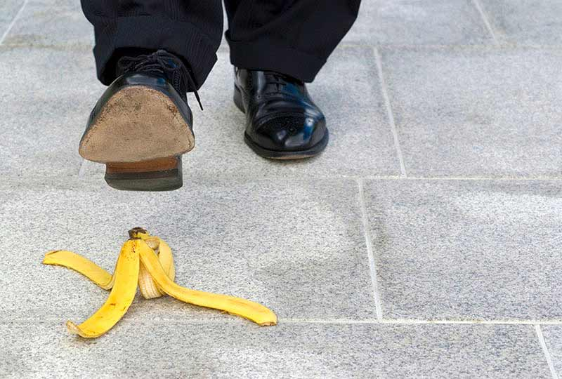 Man walking, about to step on a banana peel