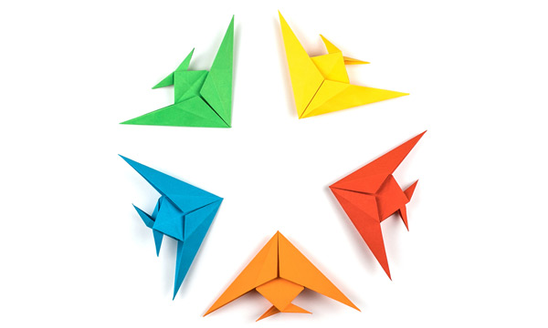 Multiple colored origami fish, all pointing to center